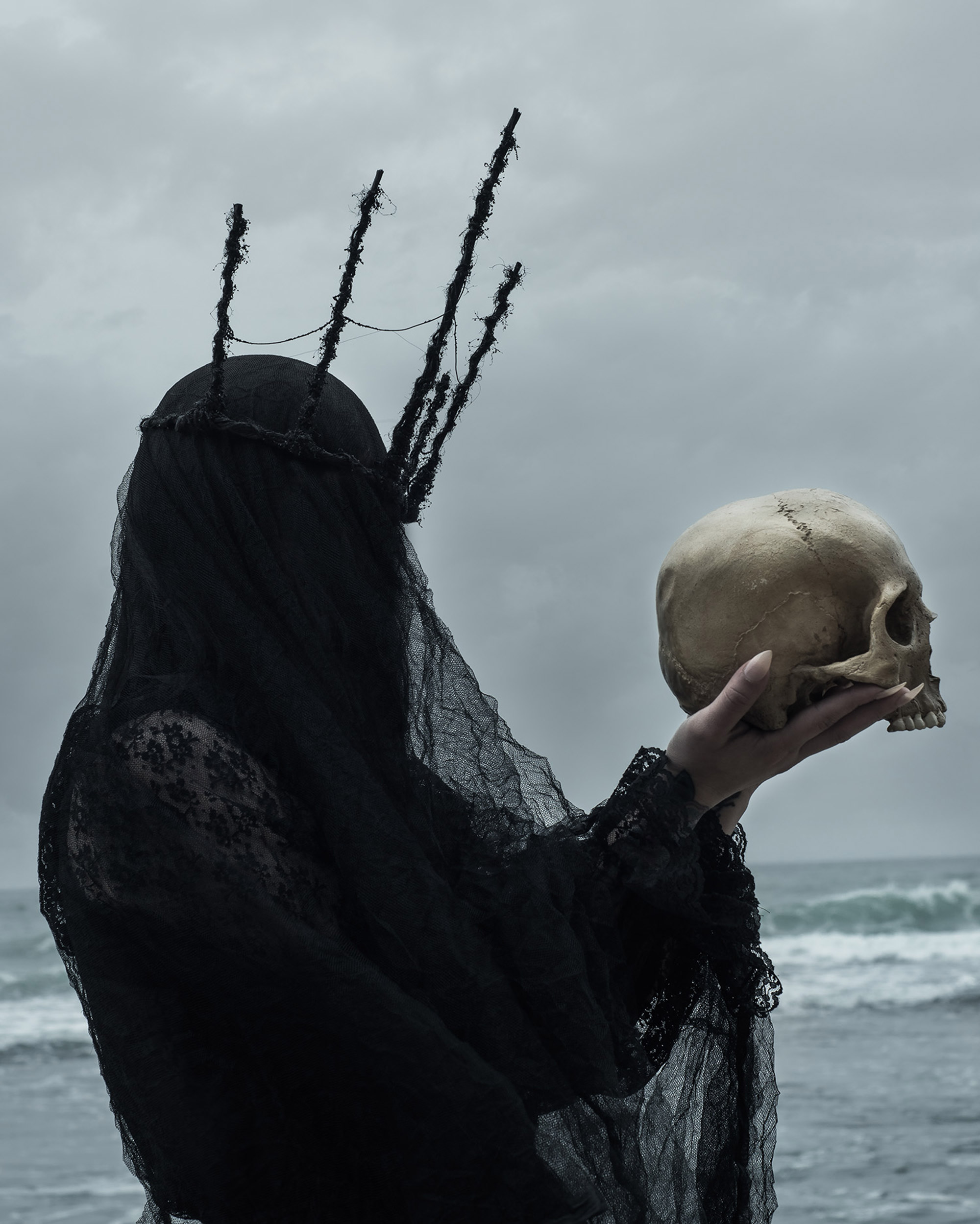 American Ghoul, Siren, dark figure holding skull on shoreline