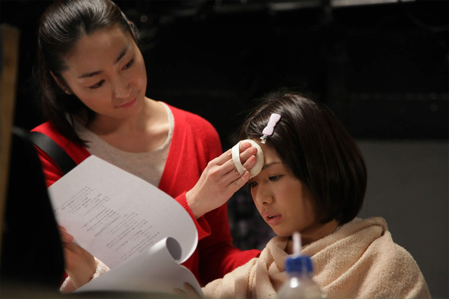 woman putting makeup on young girl, in Makeup Room (Meikurumu)