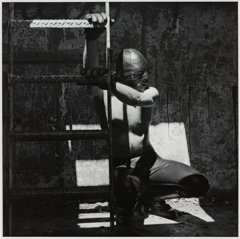 Robert Mapplethorpe - man climbing on ladder wearing S&M gear
