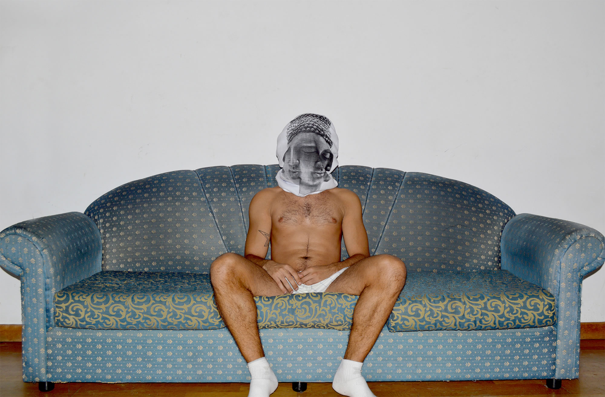 man with tshirt over head, sitting on couch