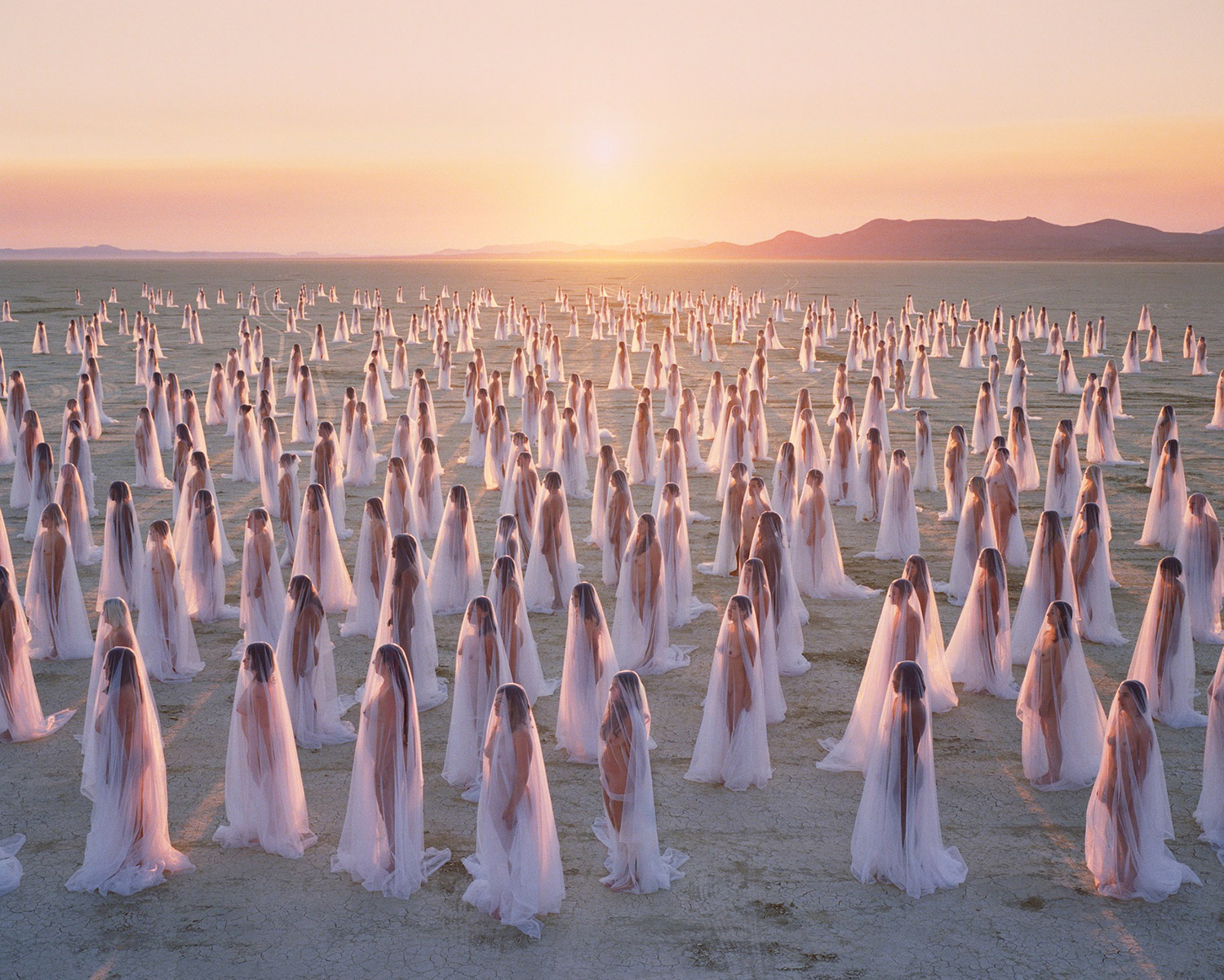 Spencer Tunick - bodies wearing gauzy fabric in Black Rock Desert, Burning Man
