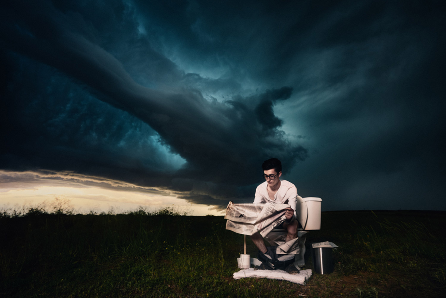Benjamin Von Wong - man on toilet in field under storm