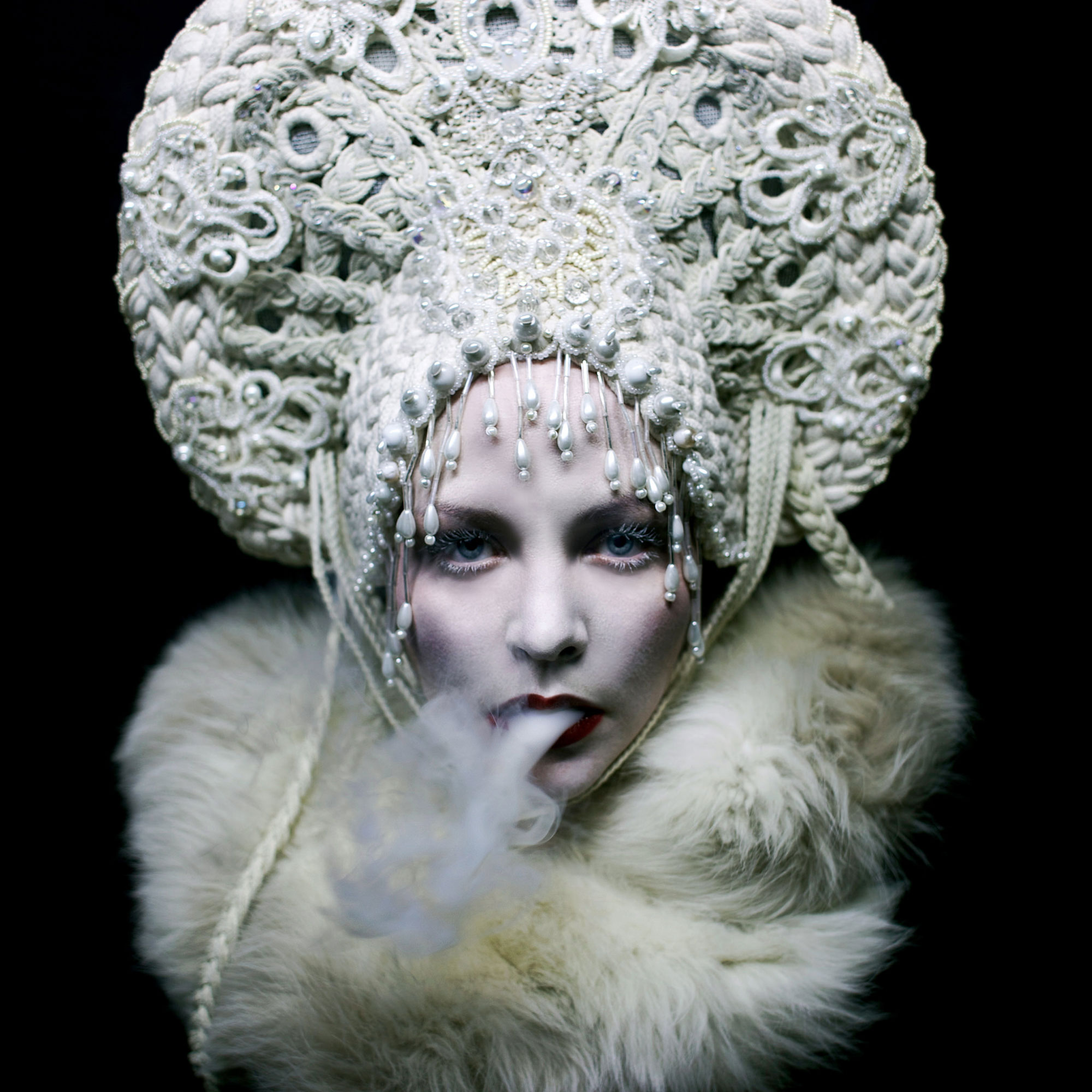Helen Warner, White Mischief - woman blowing smoking wearing white fur and crown