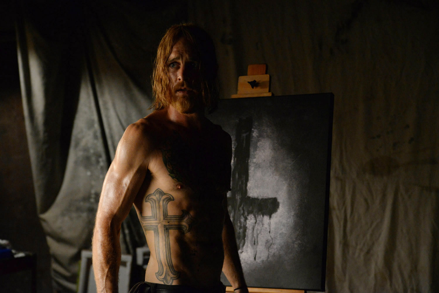 man with christ cross tattooed on body, in the devil's candy movie