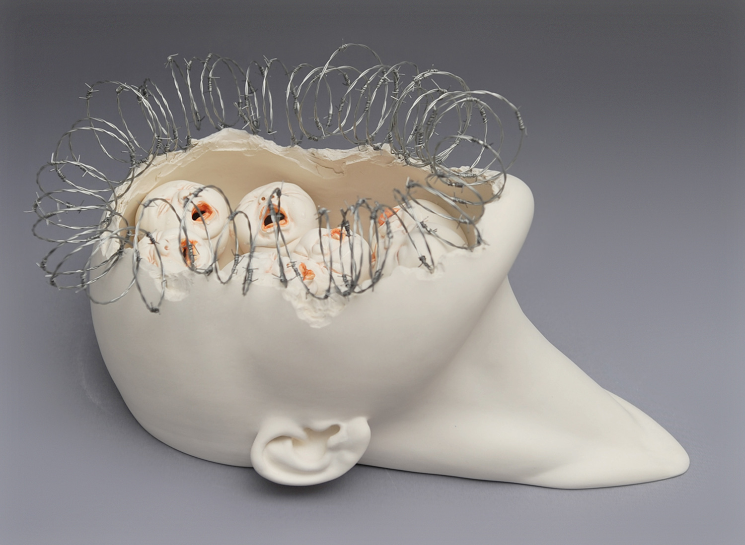 face busted open with babies inside, sculpture