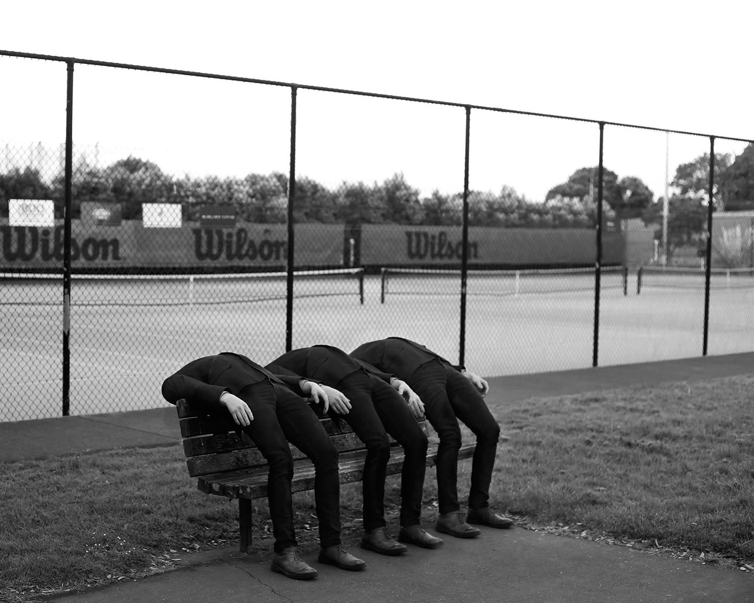 three men in black bent over bench, photography