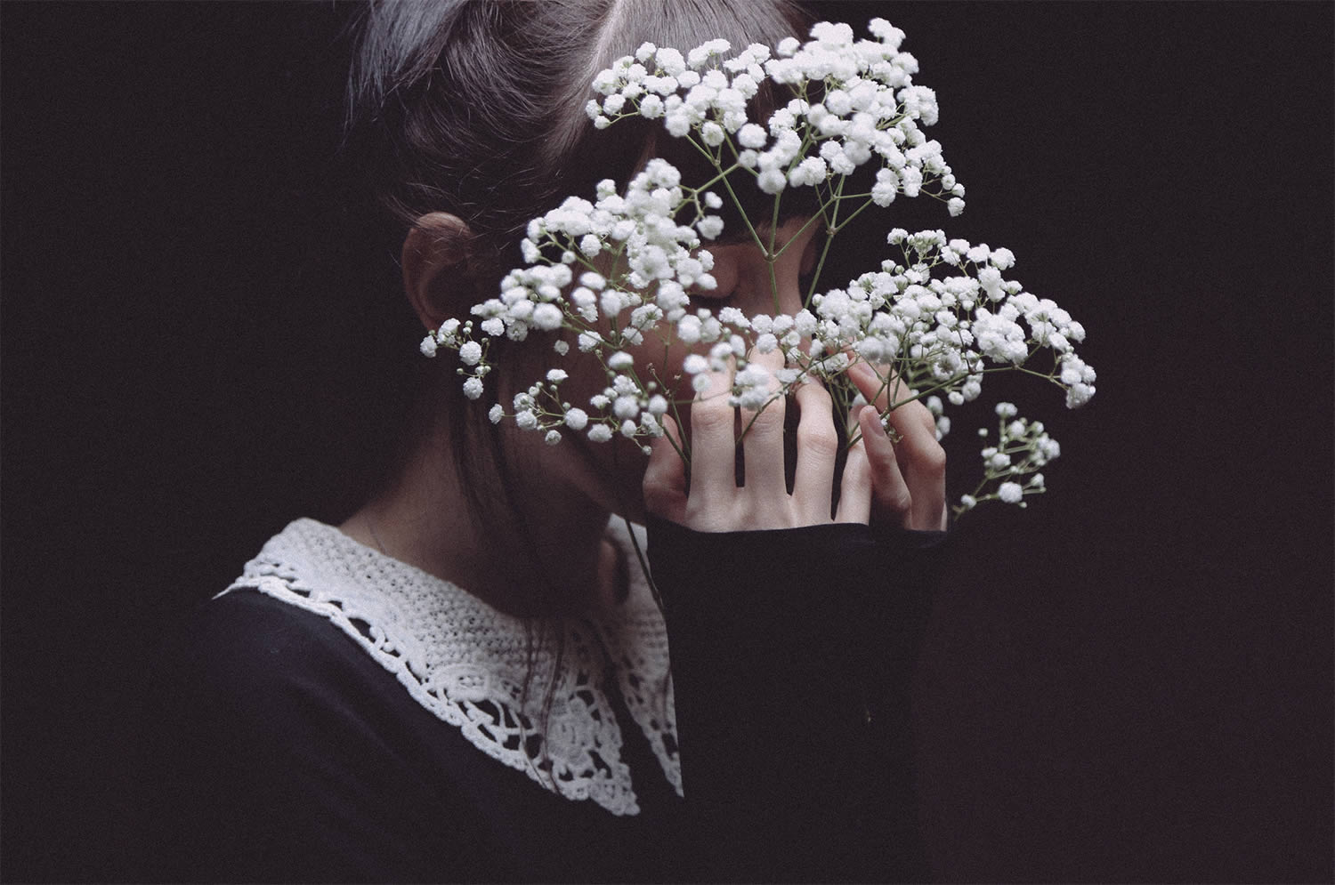 girl hiding behind white flowers