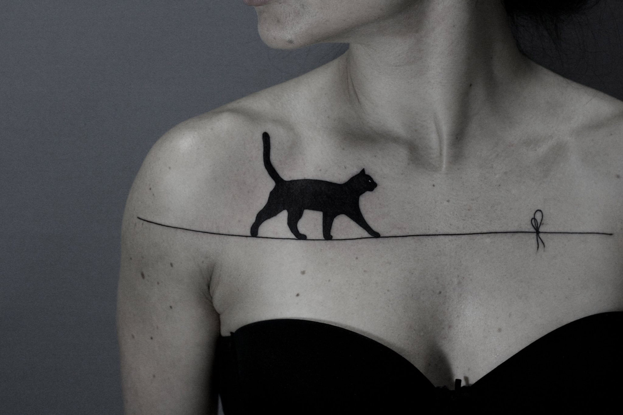 tattoo of a cat walking the tightrope