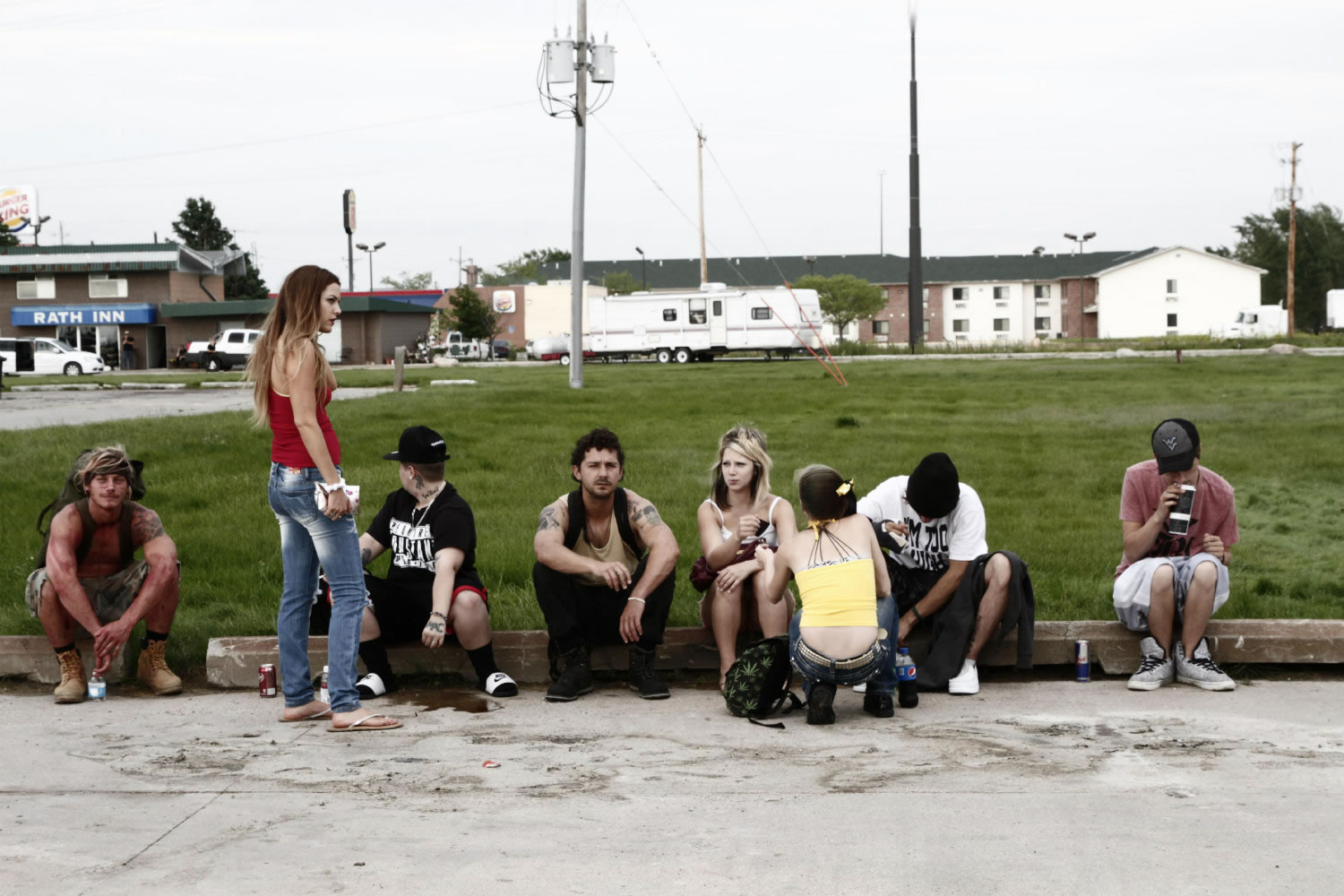young audience sitting on sidewalk, in american honey movie