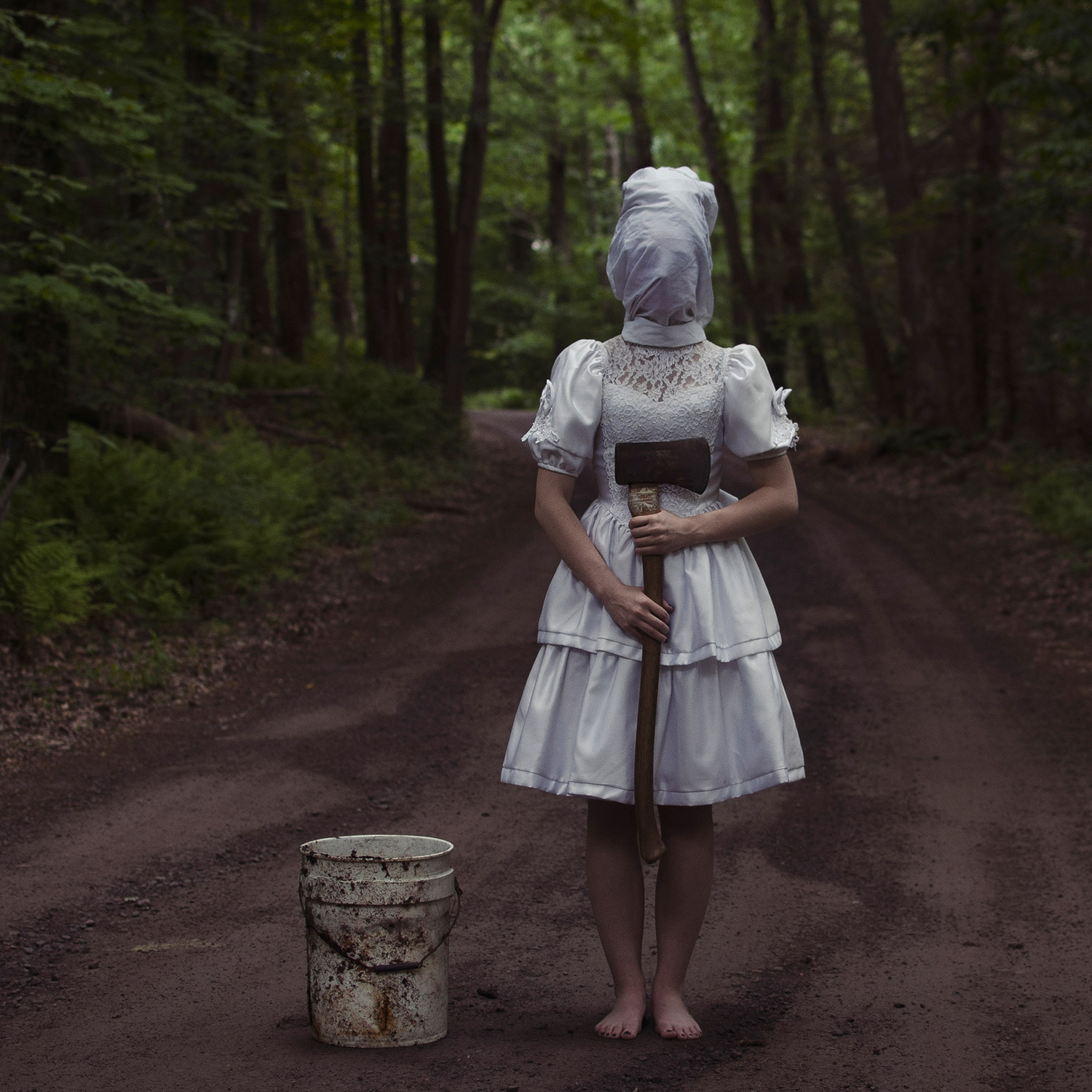 Christopher McKenney - eerie figure in dress on forest road