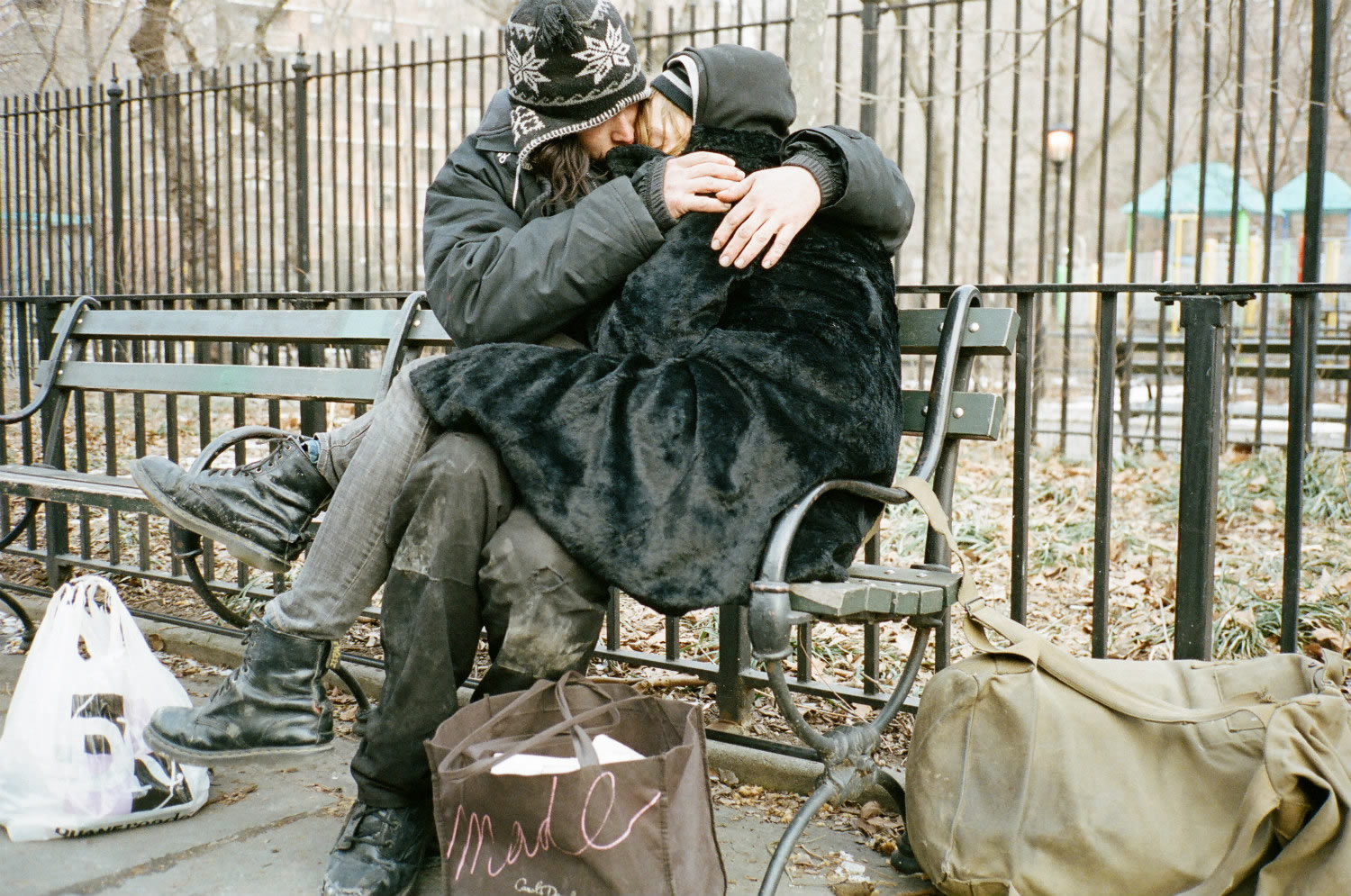 couple hugging in a street bench, heaven knows what