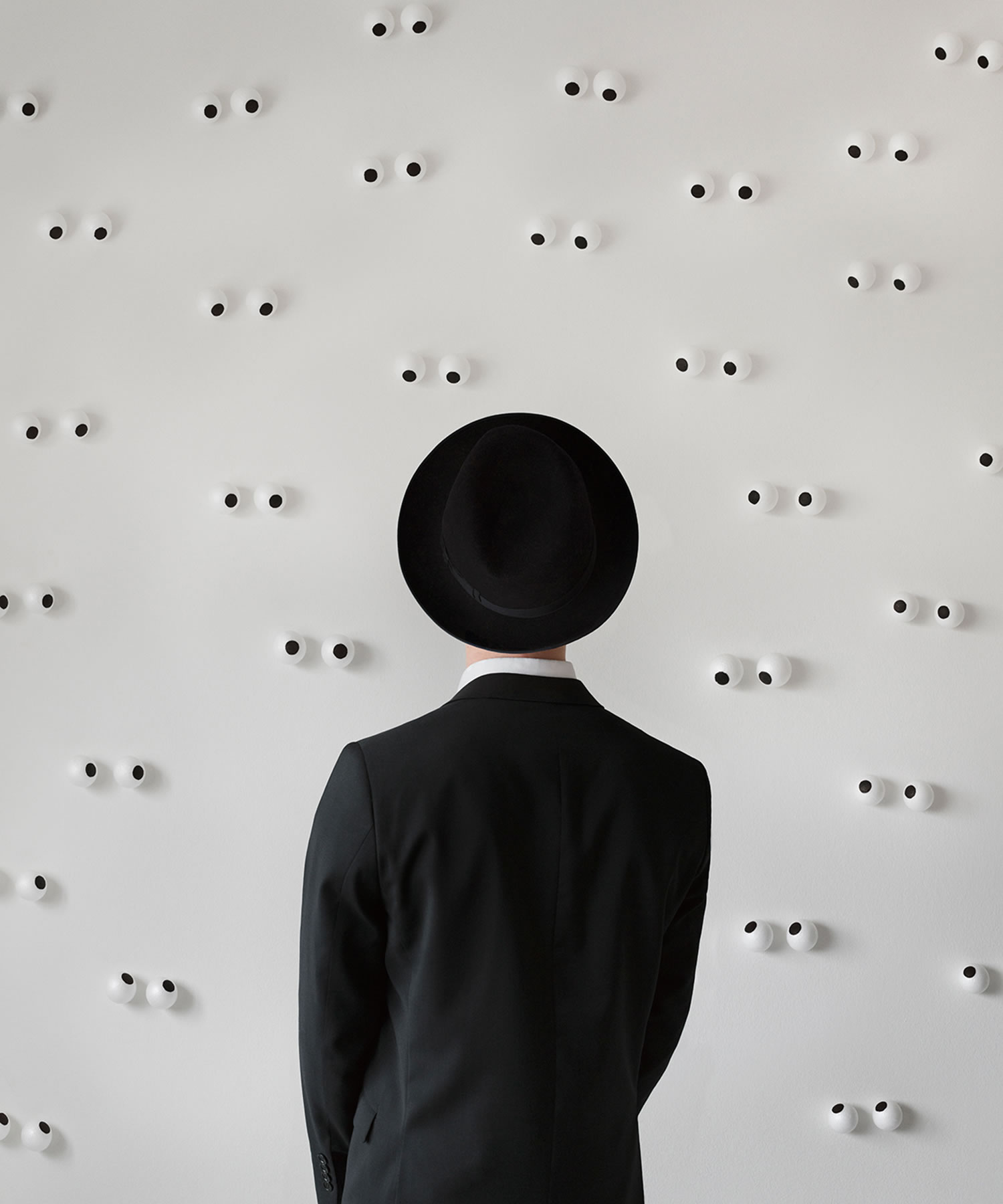 surveillance by Marcus Møller Bitsch, man with hat, and googly eyes on wall