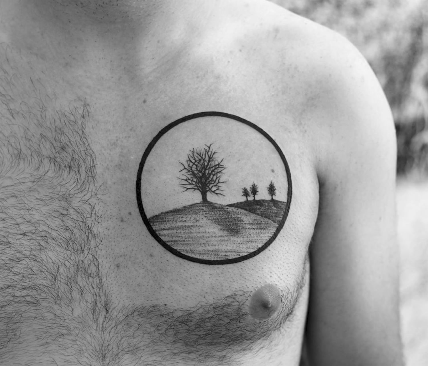 trees and grass, circle outline, tattoo on chest