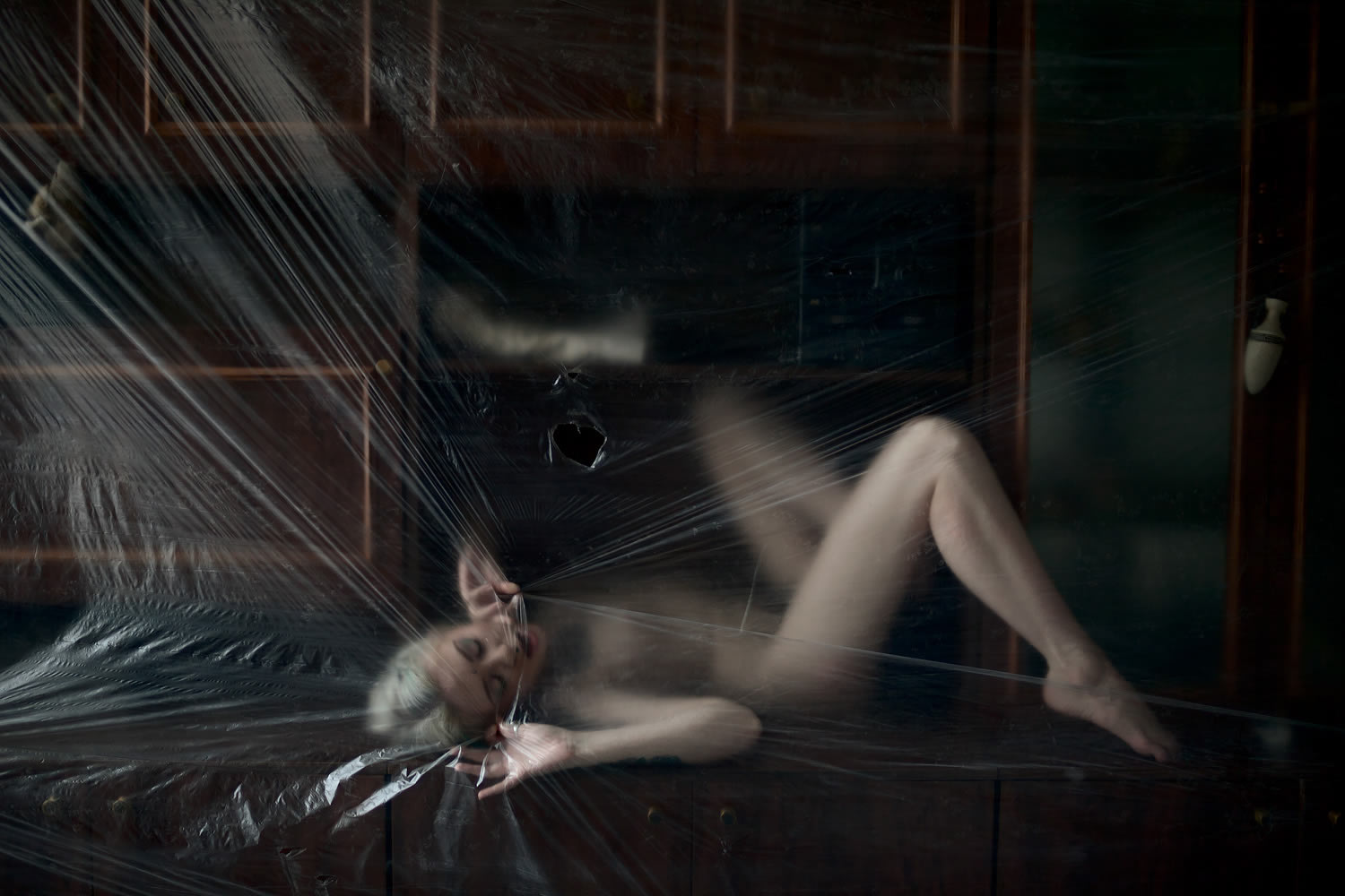 plastic sheeting over nude woman
