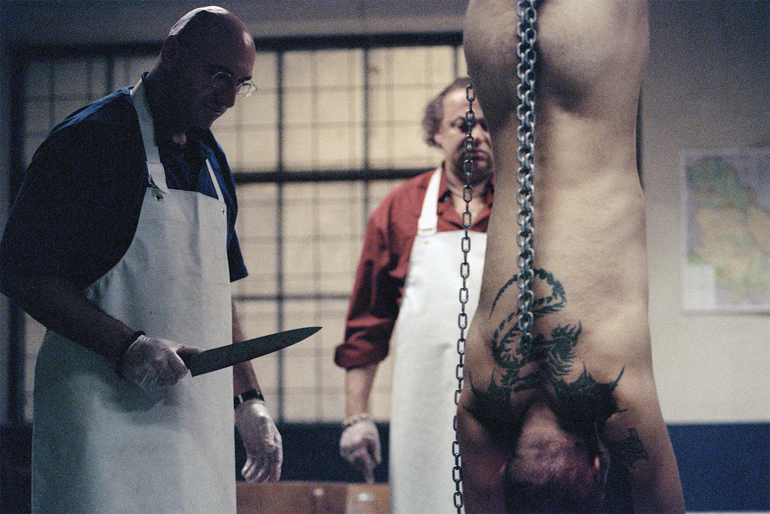 butcher with knife, man hanged upside down, in pusher 1996