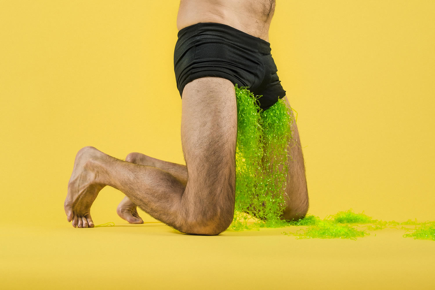 green liquid flowing out of men's shorts, photography