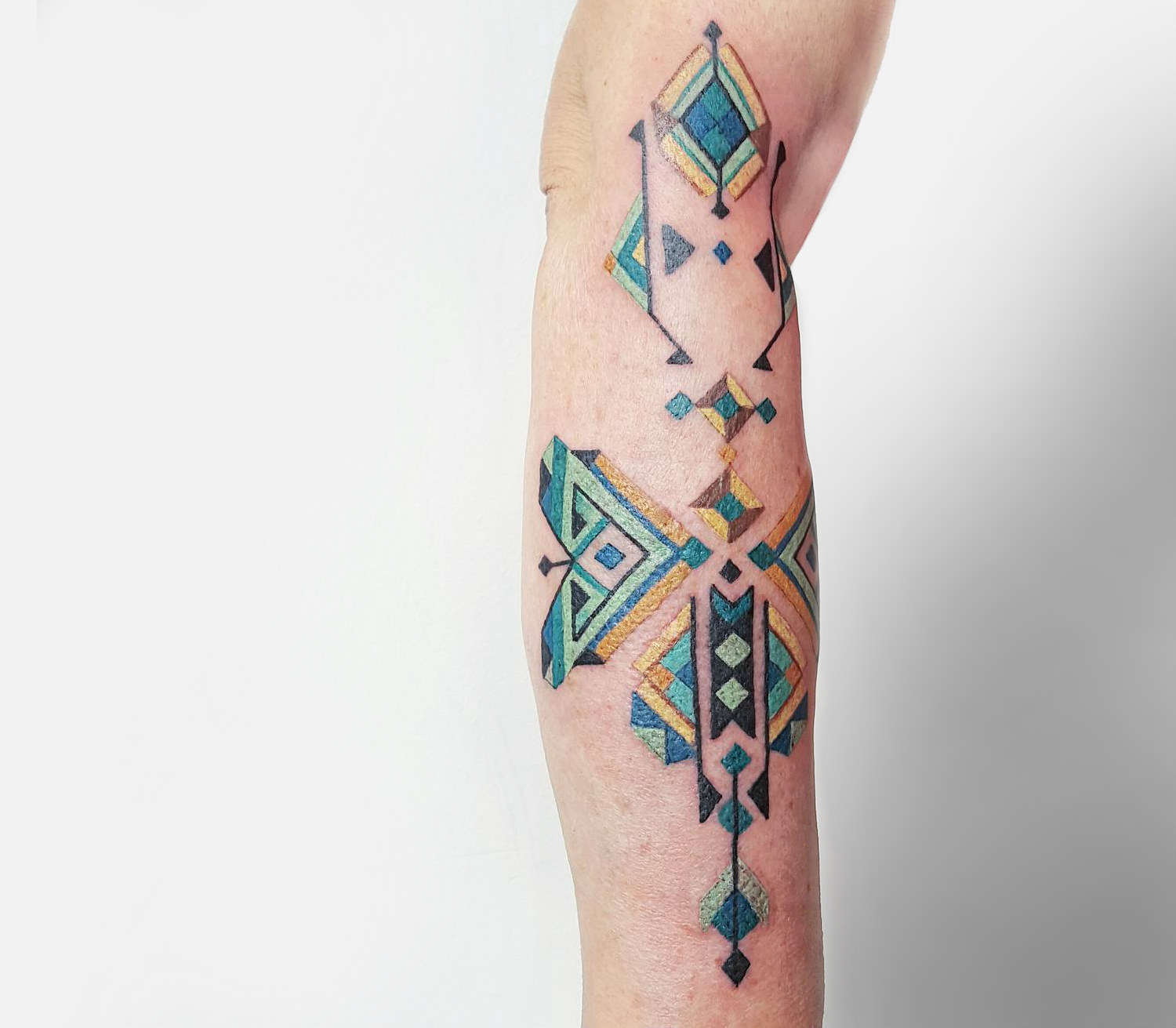 Brian Gomes blue and green geometric tattoo