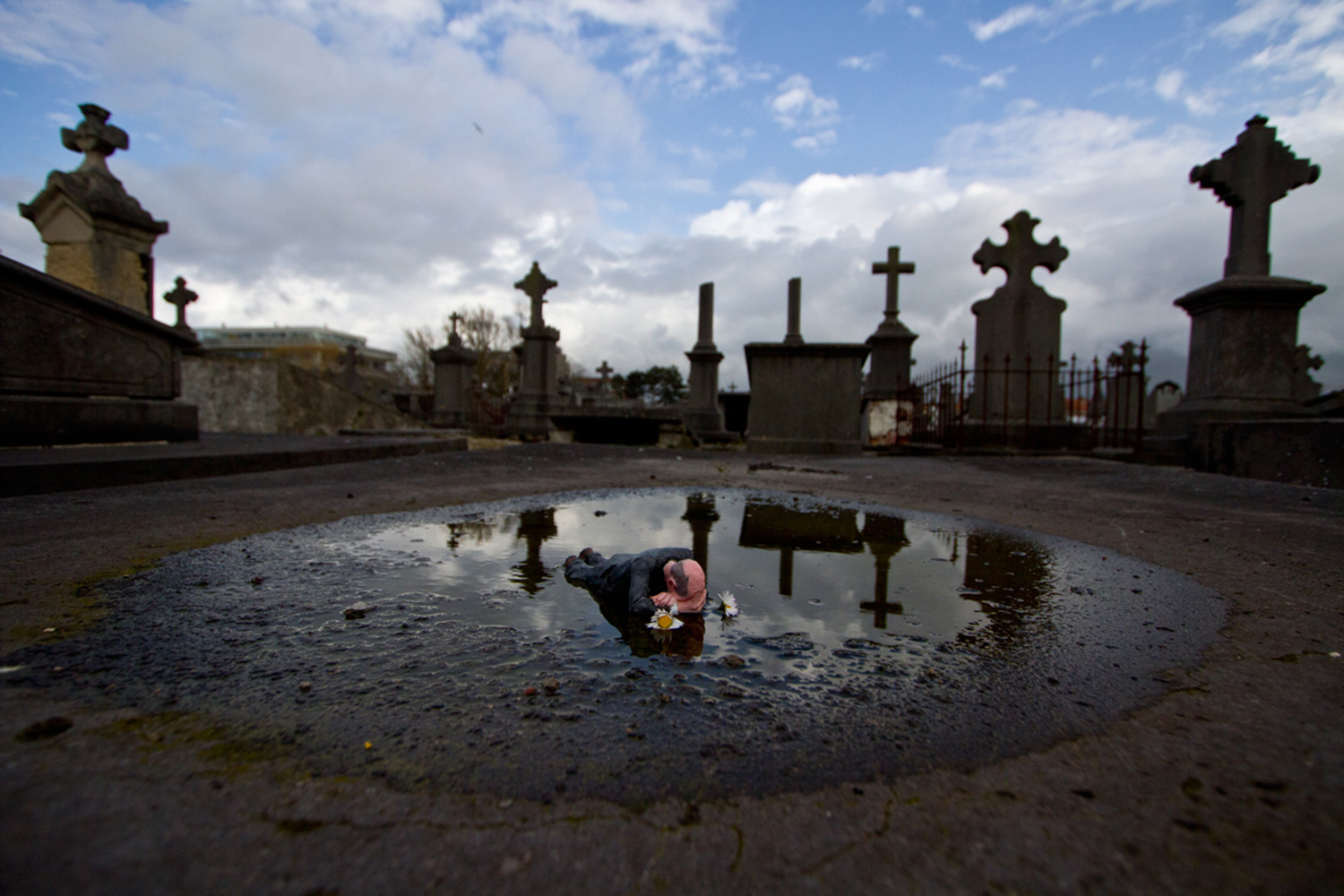 Isaac Cordal - graveyard, lying in puddle