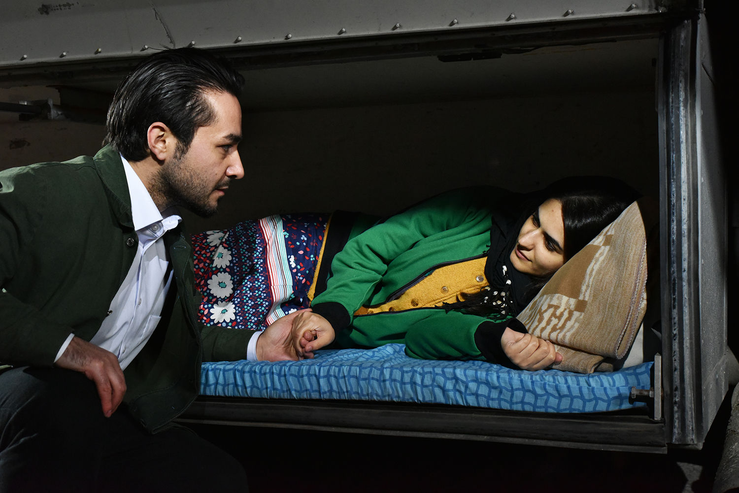man talking to a woman lying on train bed, The Other Side of Hope