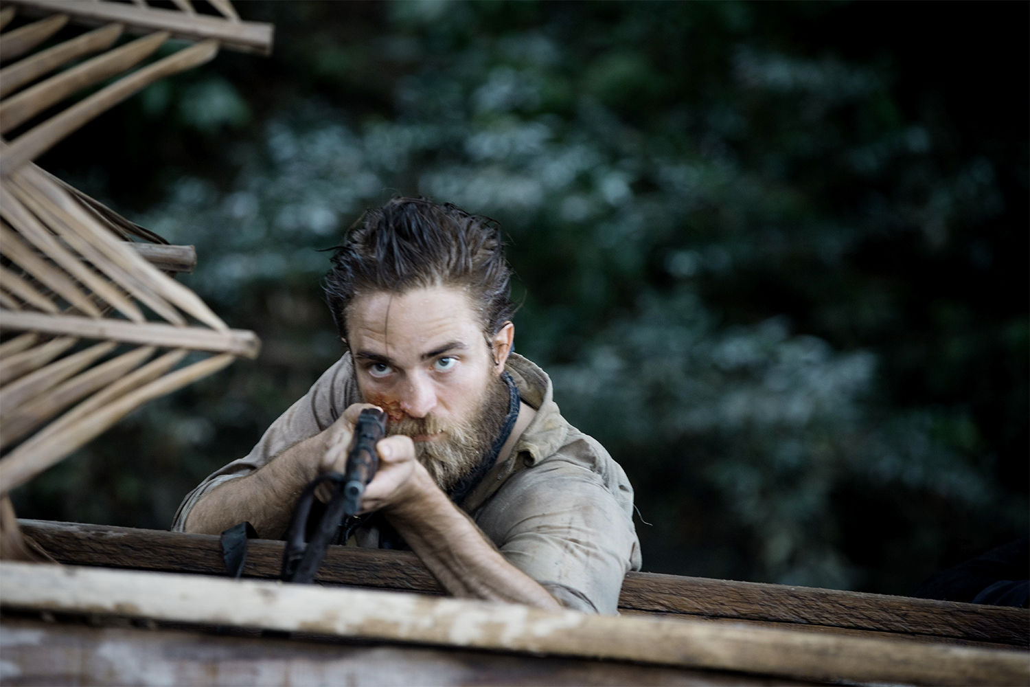 Robert Pattinson holding a rifle in the lost city of z