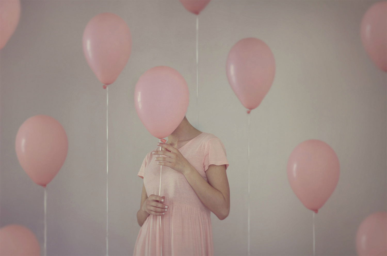 woman hidden in pink balloons