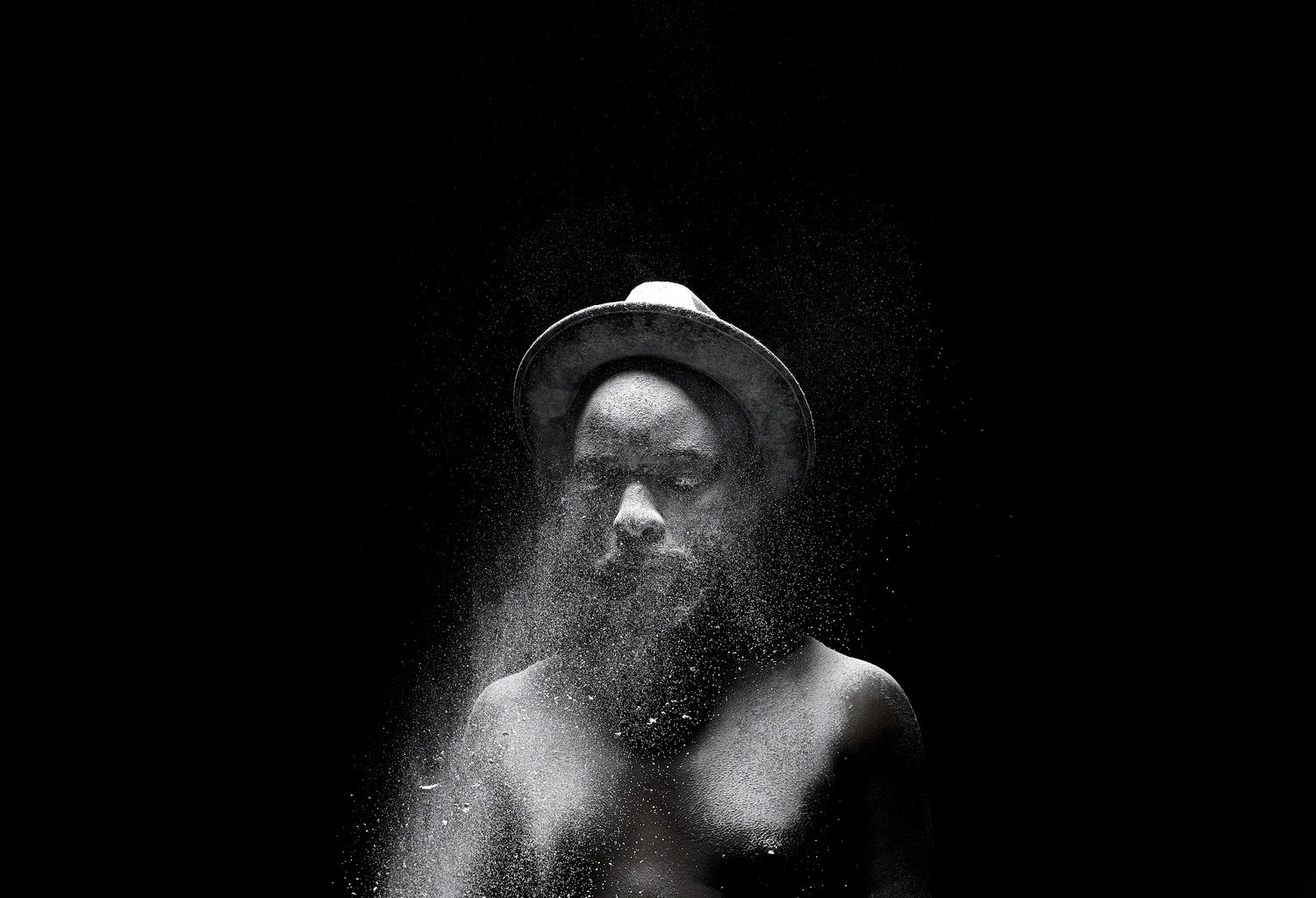 Man standing with splashes of water in his face