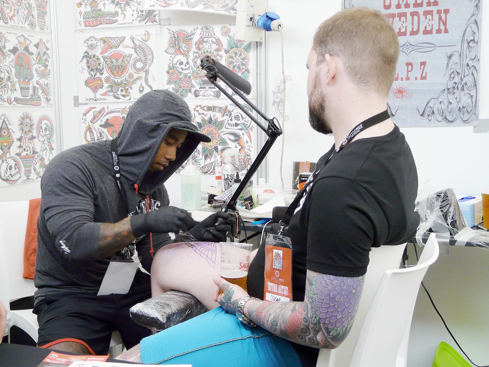 filip henningson tattooing a client's leg