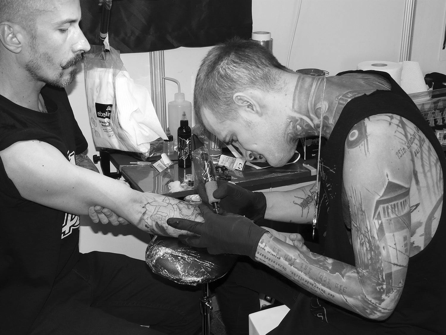 Neon Judas tattooing client's arm