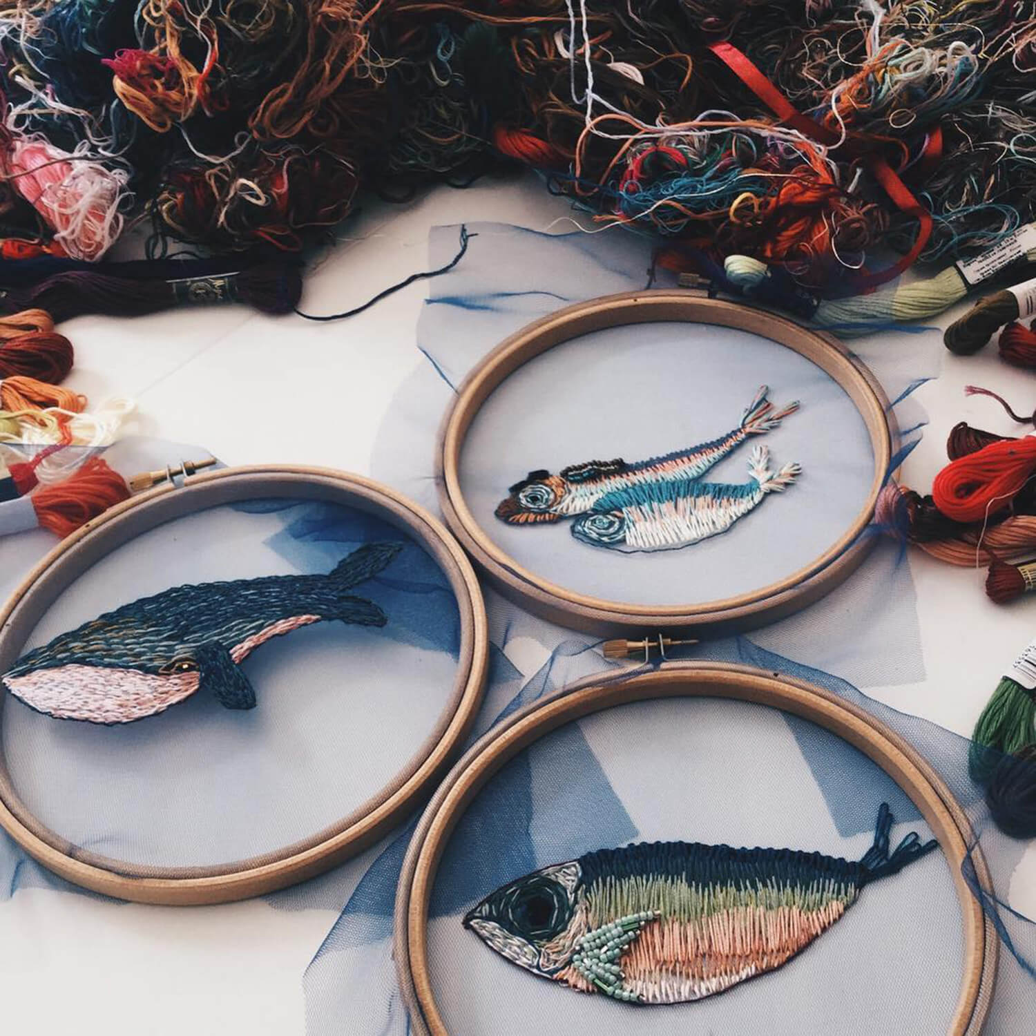 embroidery of sea creatures stitched within embroidery hoops
