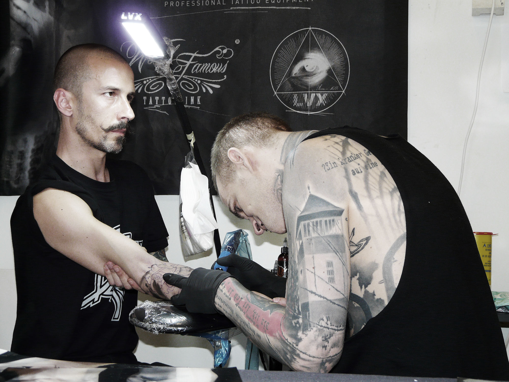Neon Judas tattooing client at a tattoo convention