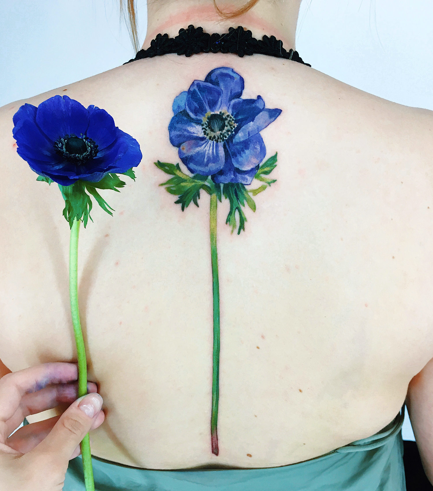 blue flower tattoo on back, live leaf