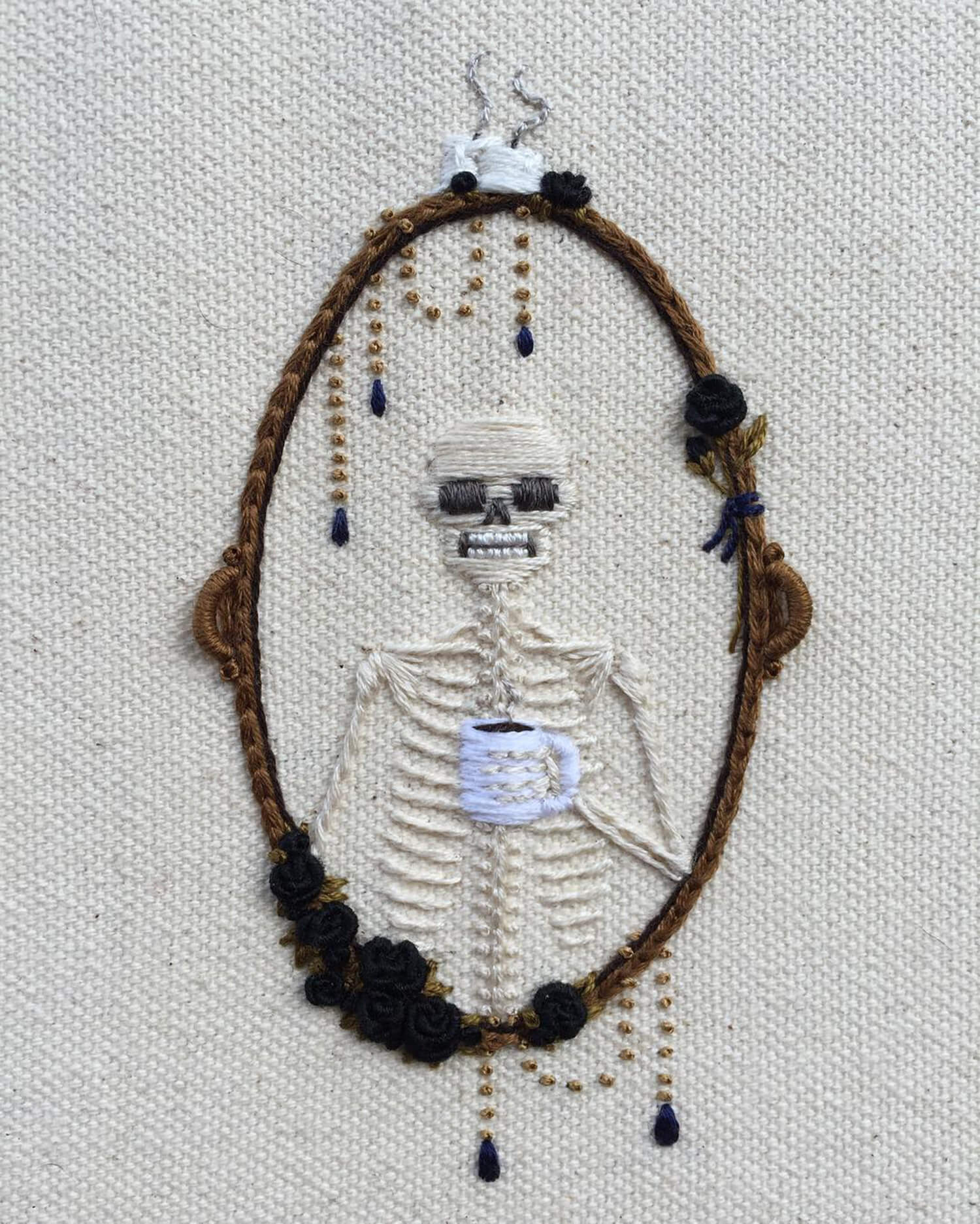 embroidered skeleton portrait holding a cup