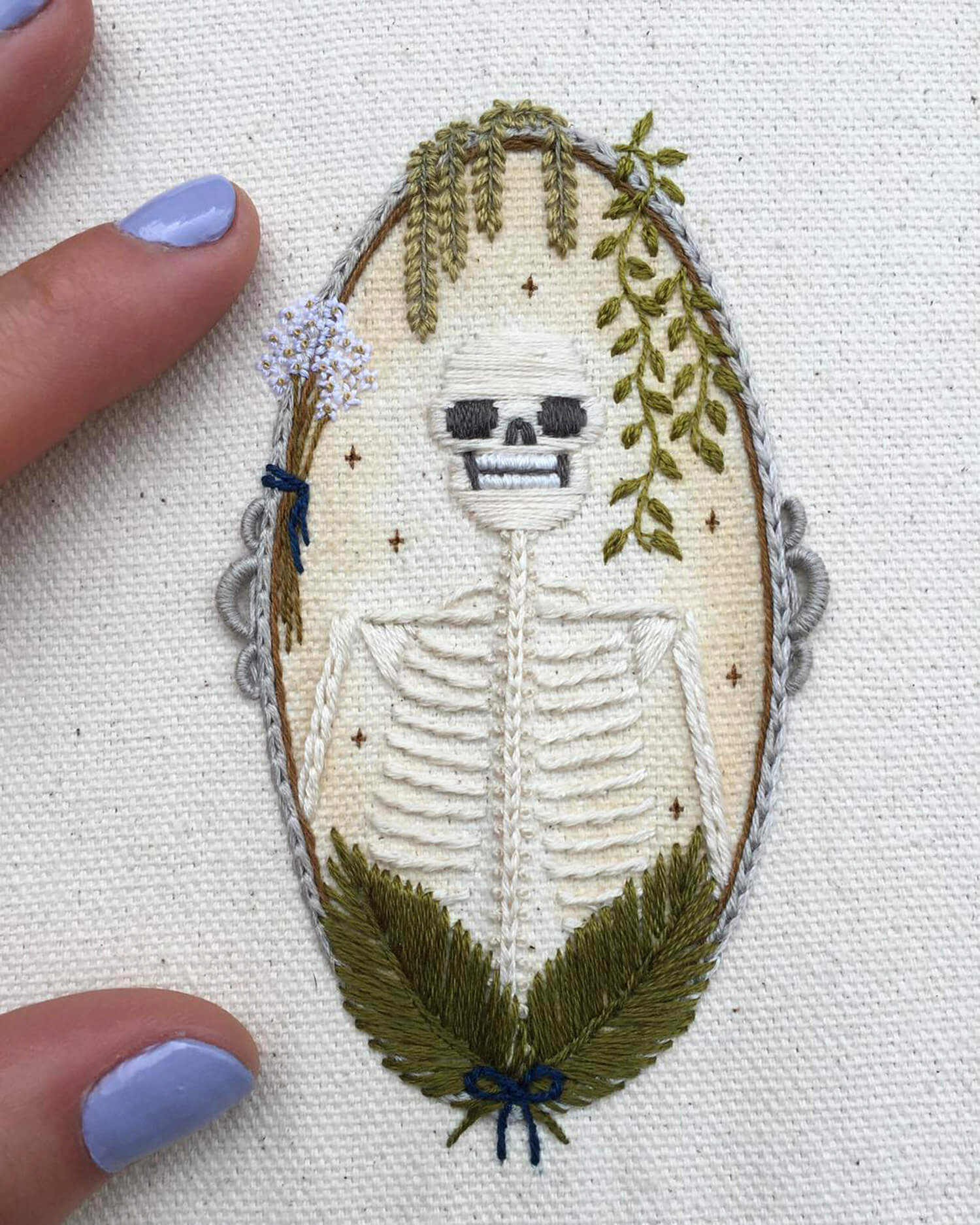 embroidered skeleton portrait surrounded by leaves