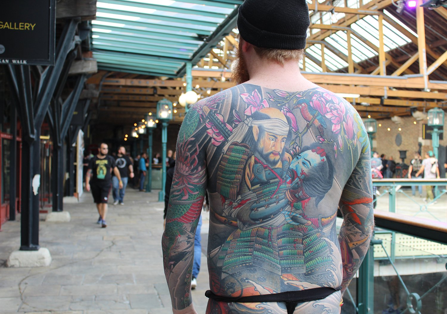 spectator with asian style tattoo on back, at convention