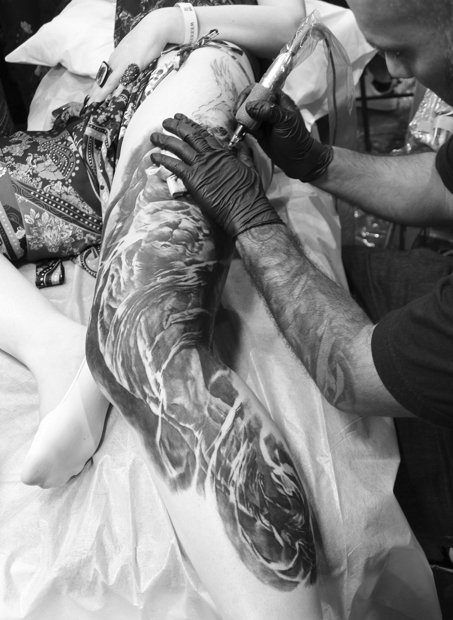 carlos torres tattooing a leg, realism tattoo, black and grey