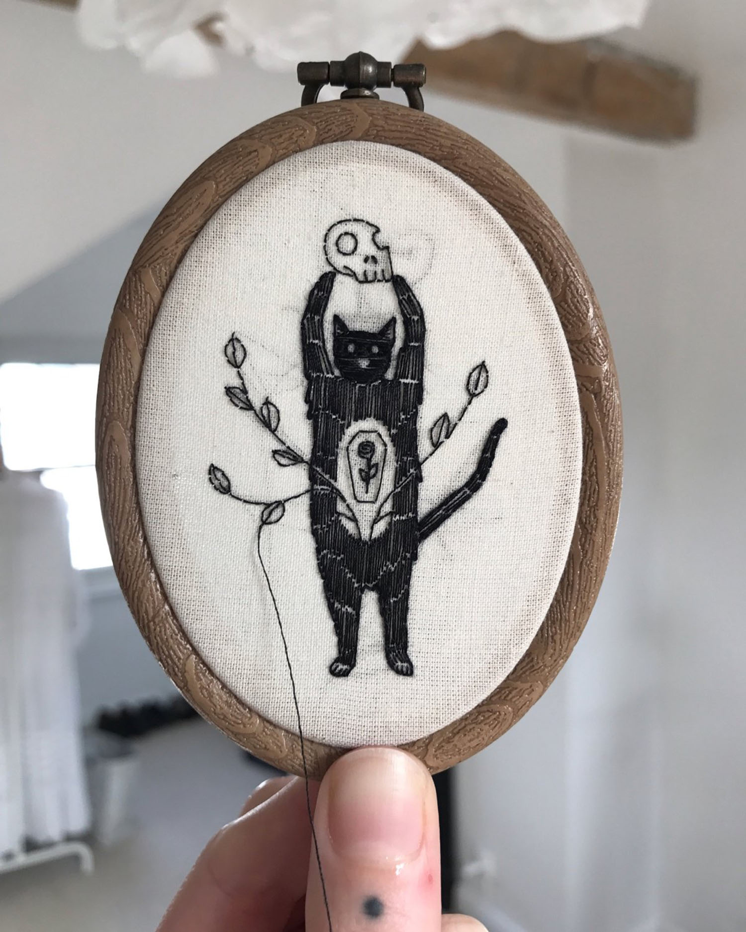 Embroidery of a cat holding a skull