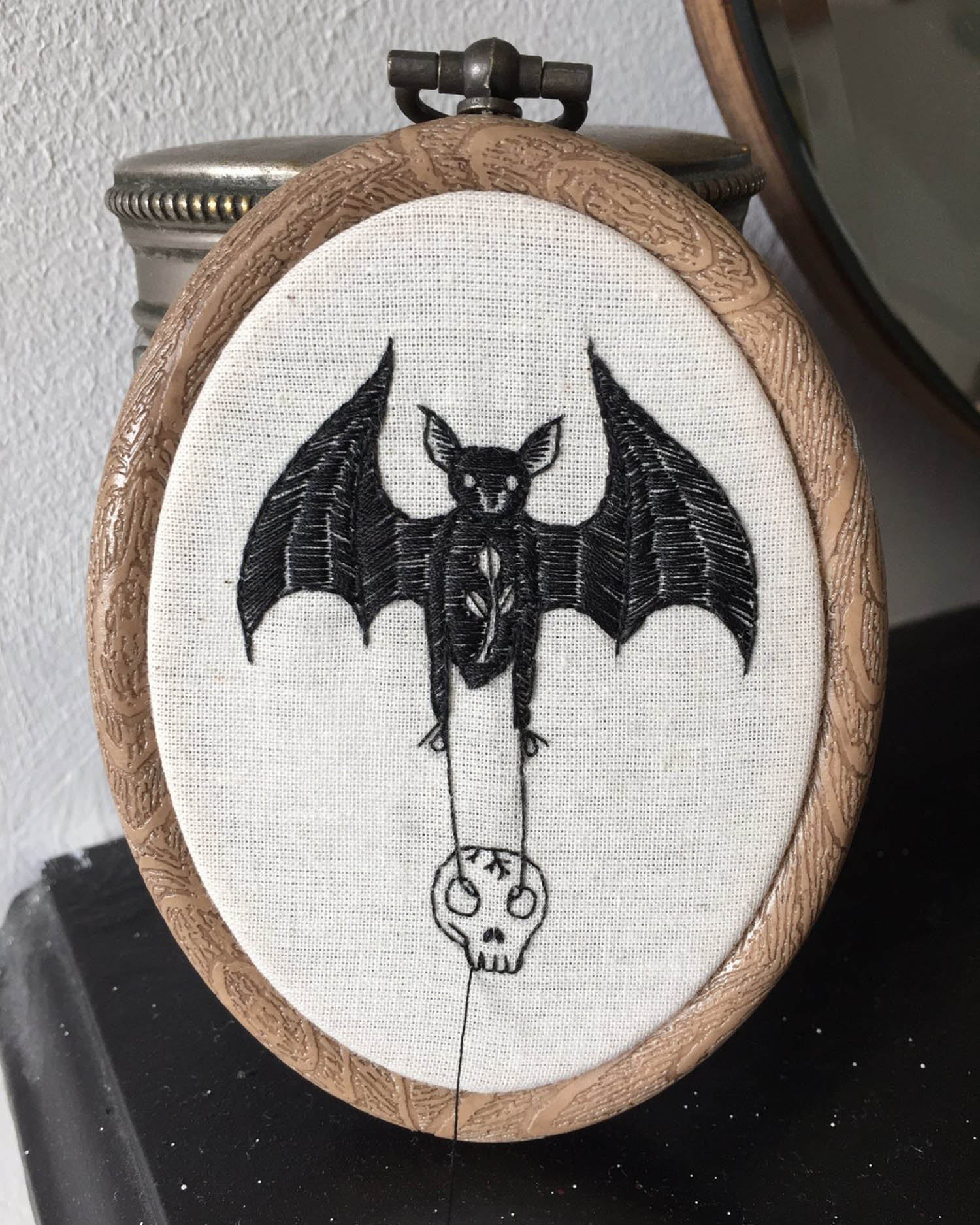 Embroidery of a bat holding a skull