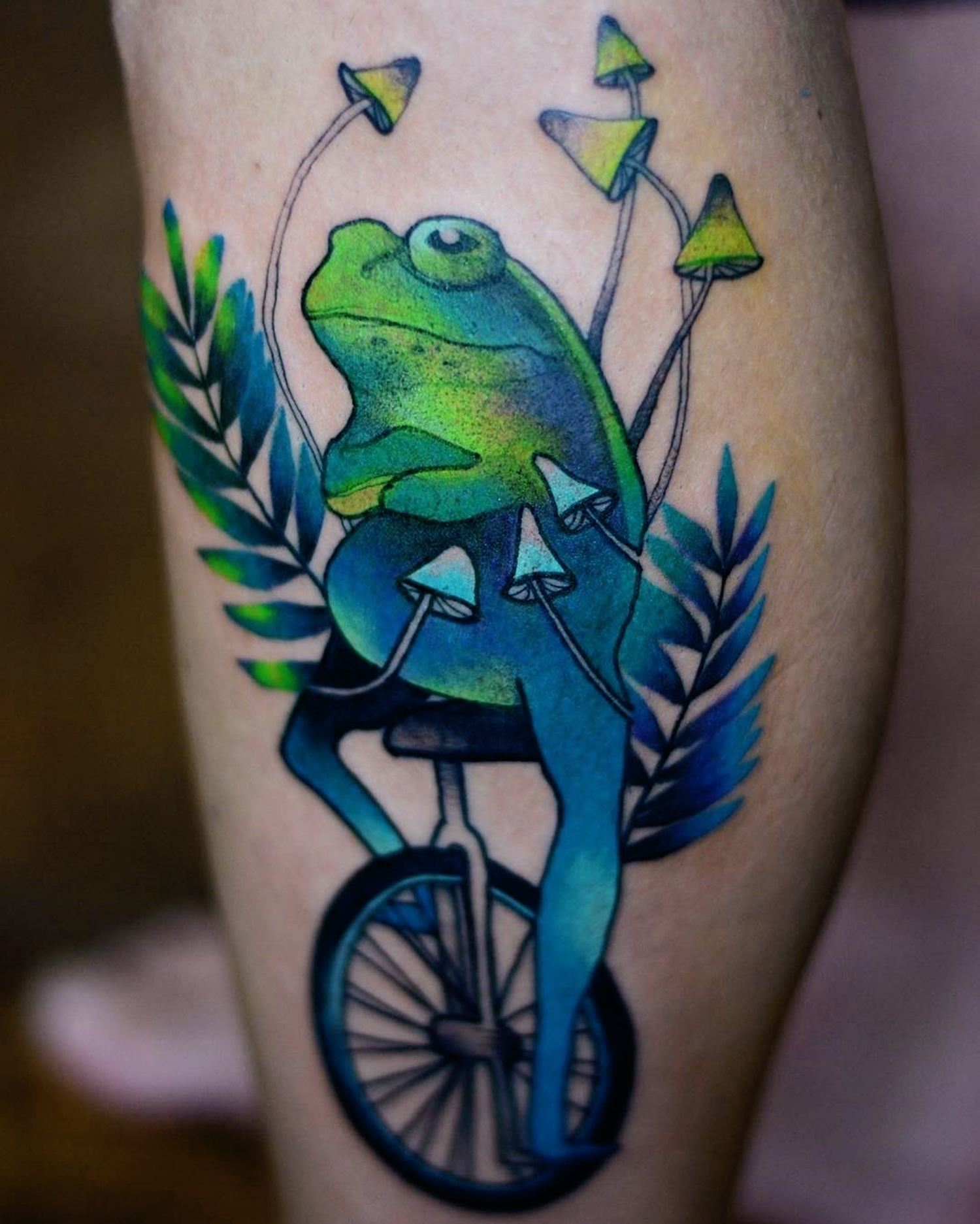 green frog on unicycle tattoo and mushrooms