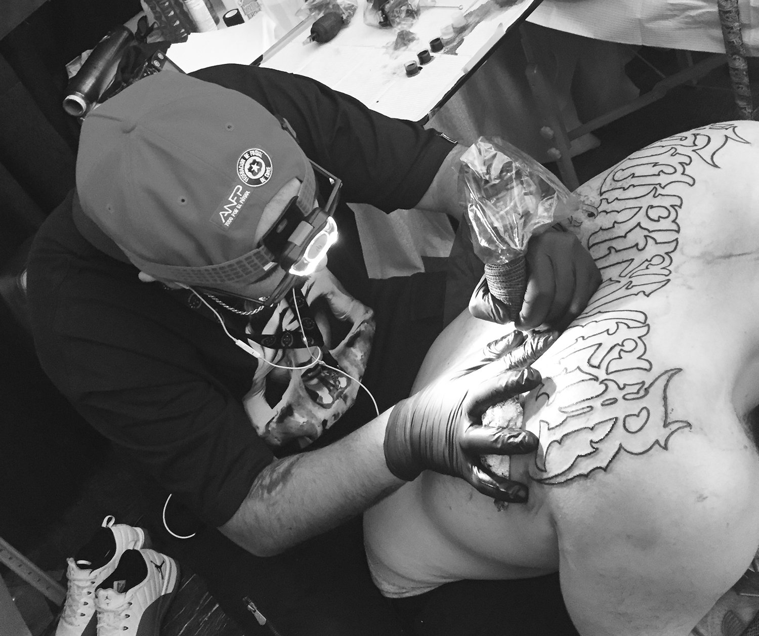 getho tattooing a large script piece on back, tattoo conventions