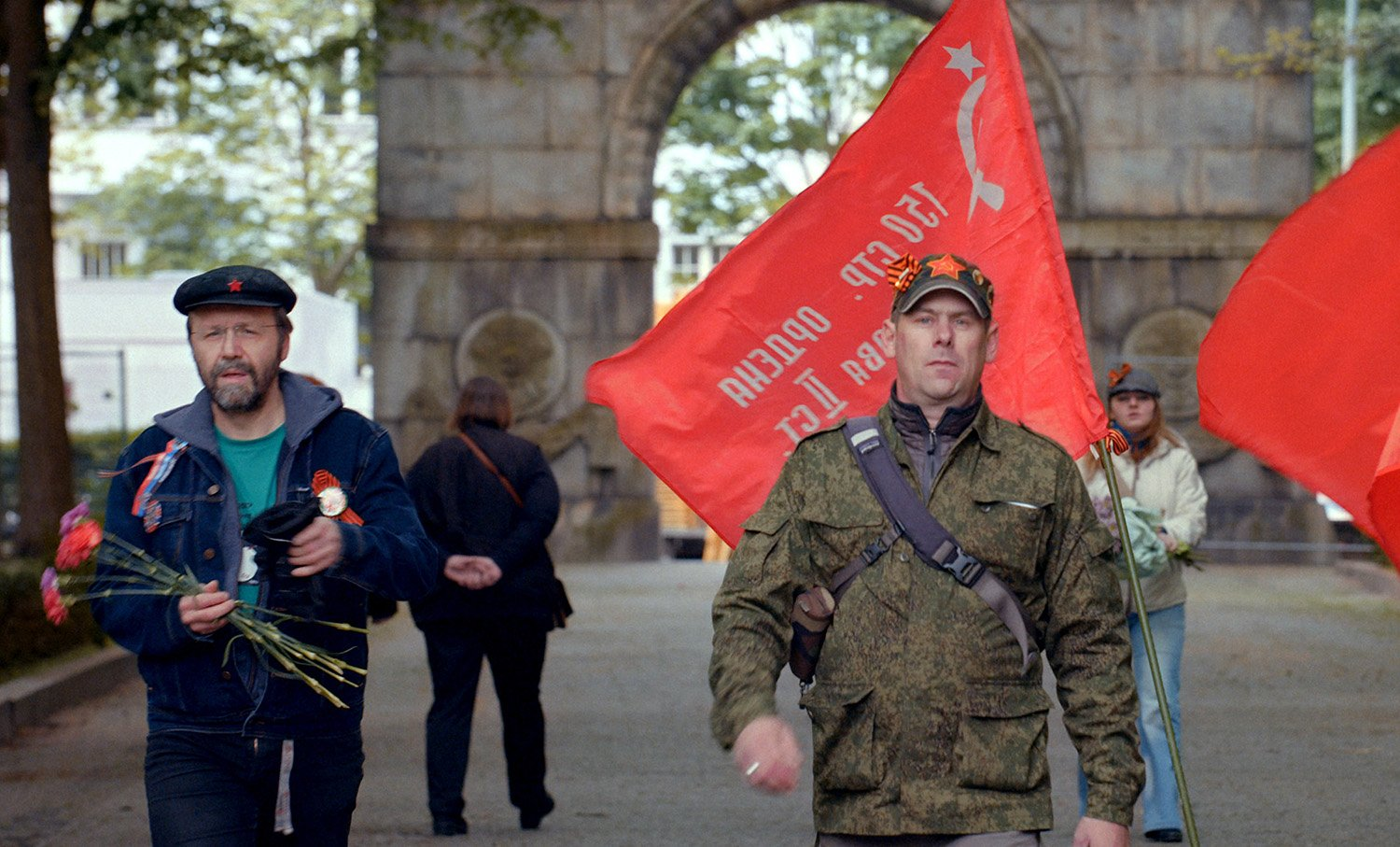red flags in background, army style guy, victory day movie