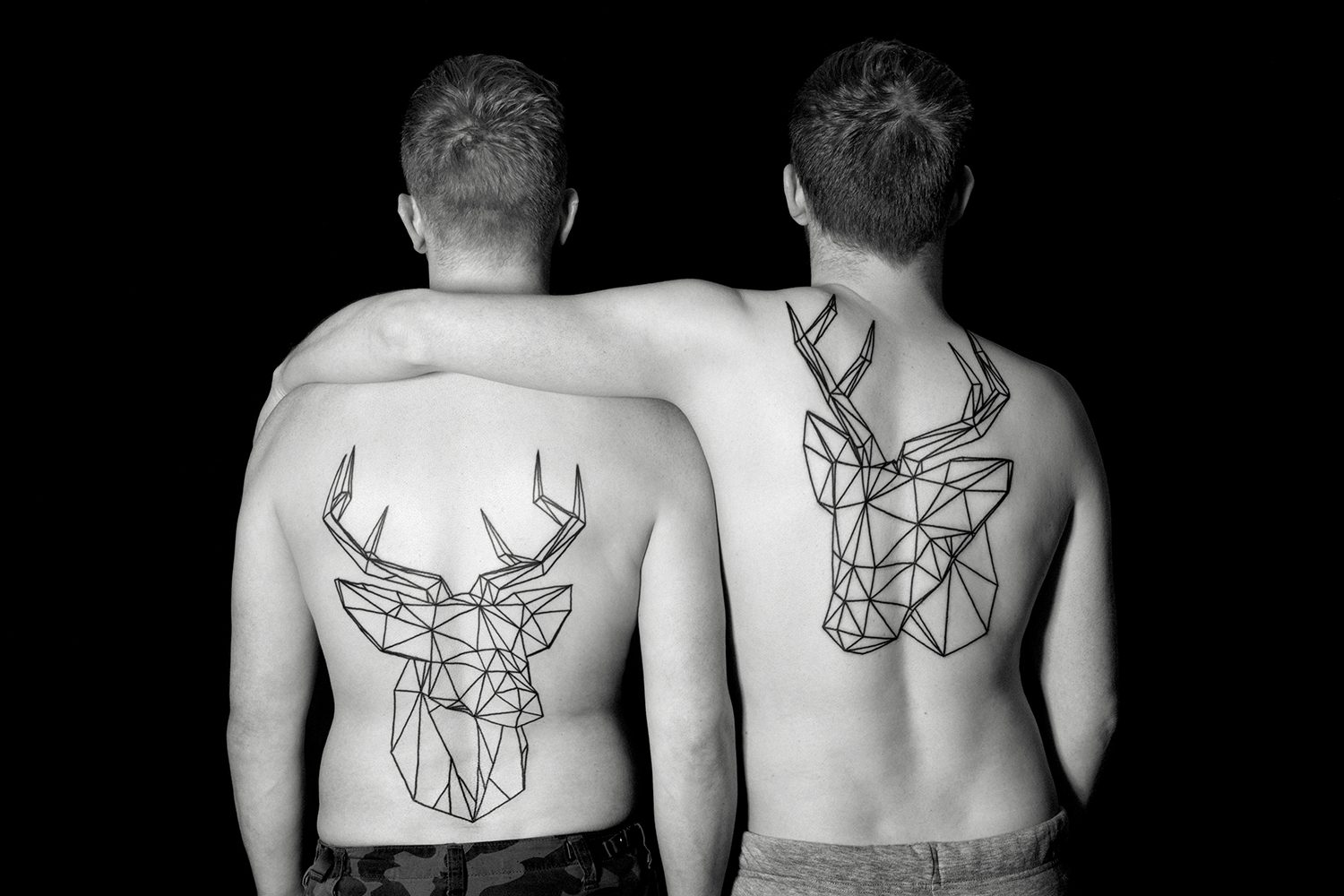 stag tattoos on back, two men. photo © erik weiss