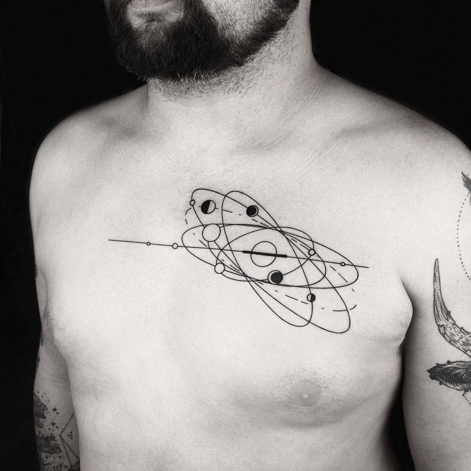 Okan Uckun - orbit chest tattoo