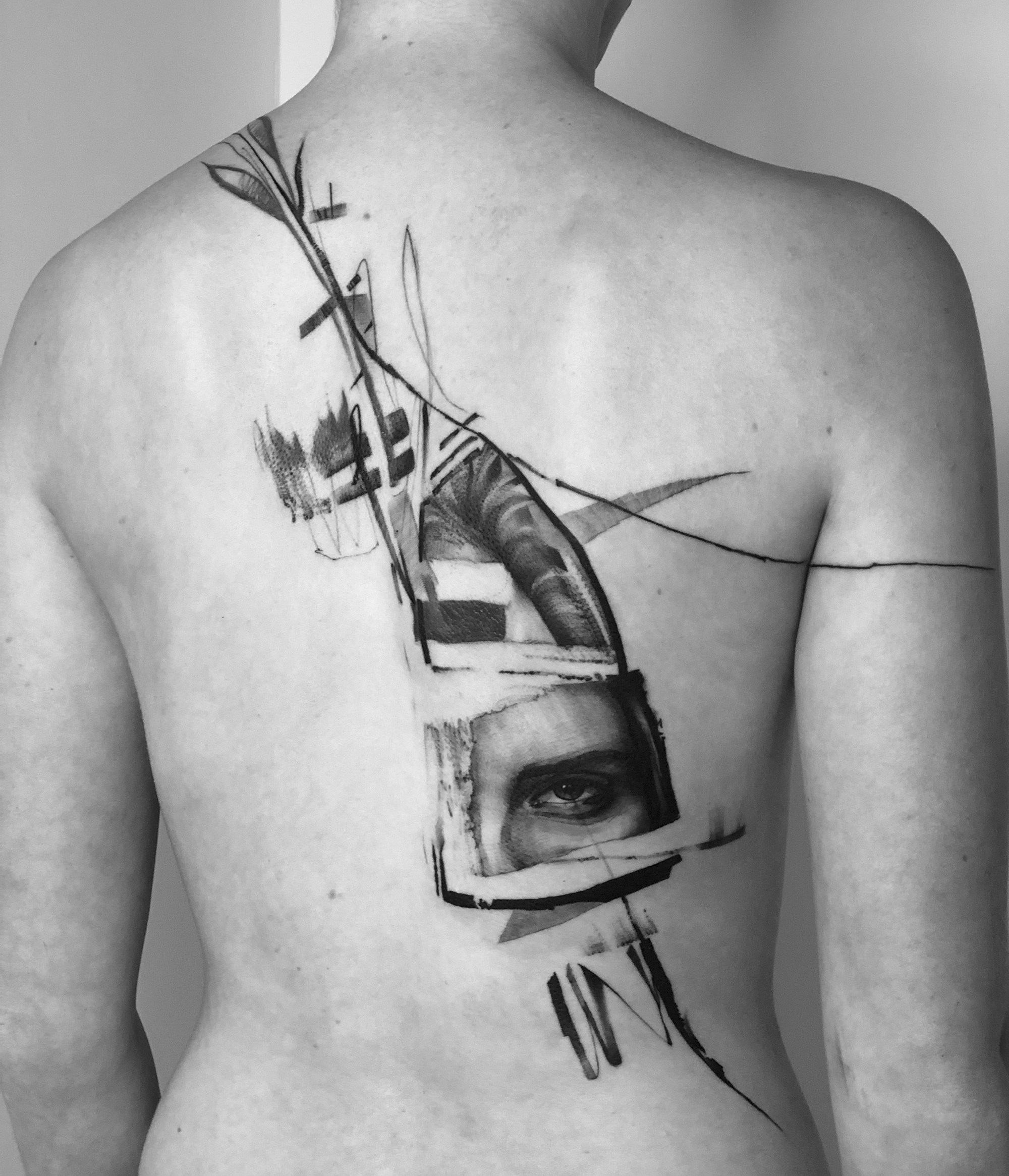 abstract tattoo on back, black and grey