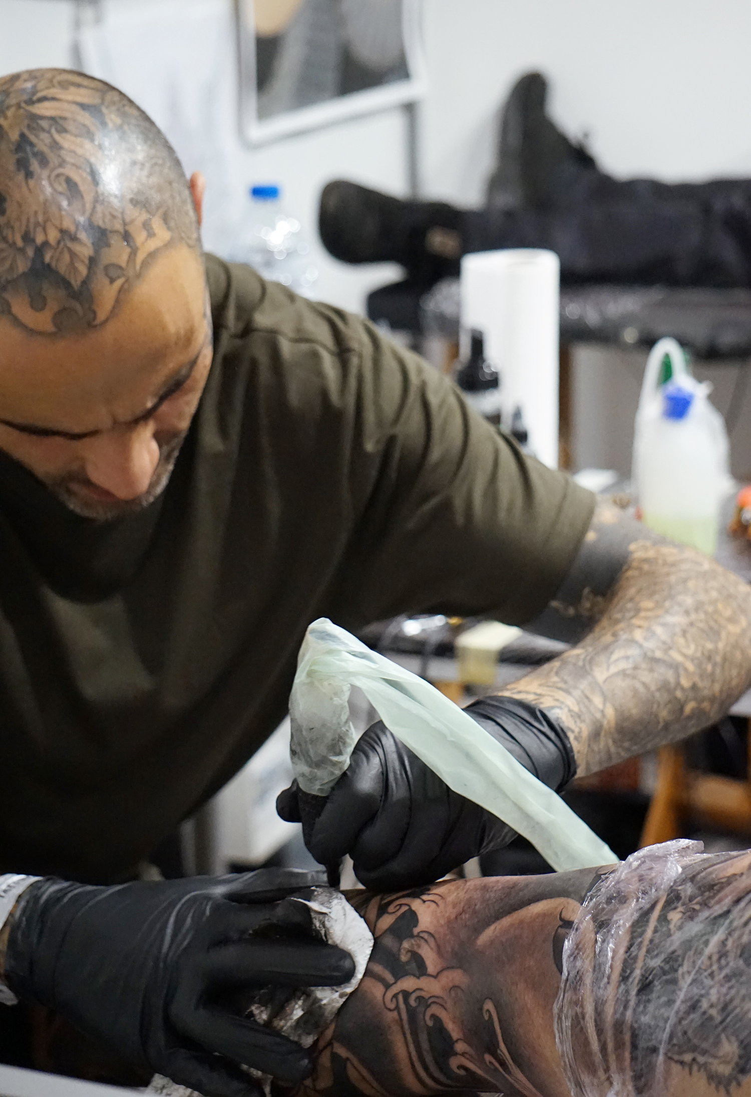 tattooer Alberto Solposto adding a Tibetan skull on the bodysuit.