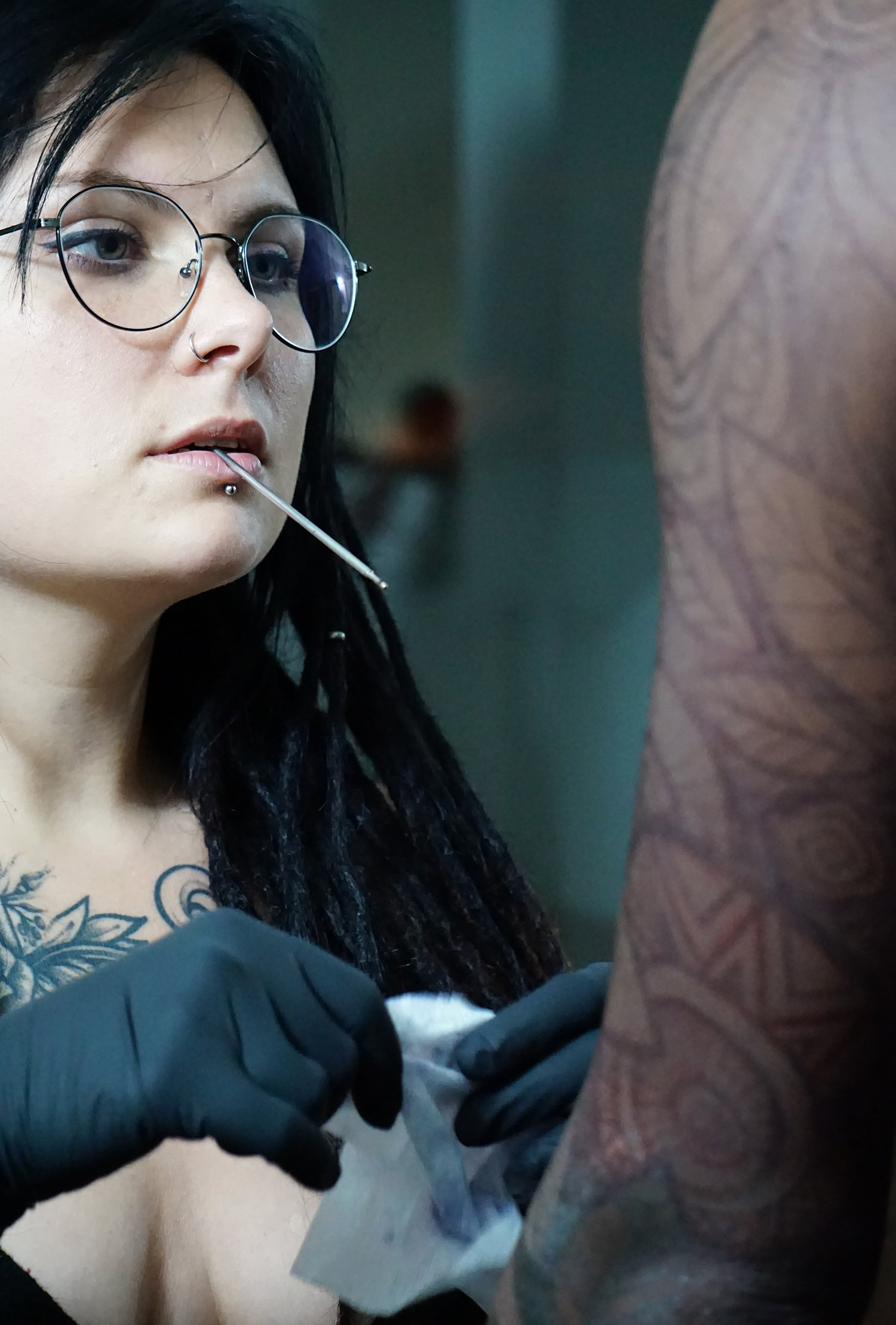 yanina viland freehanding a tattoo on a dark-skinned client