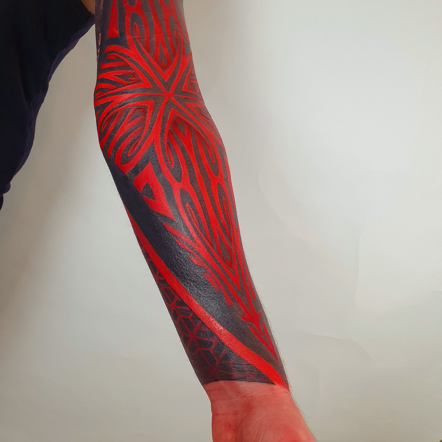arm sleeve in ornamental, geometric style red and black inks, innovative tattoo