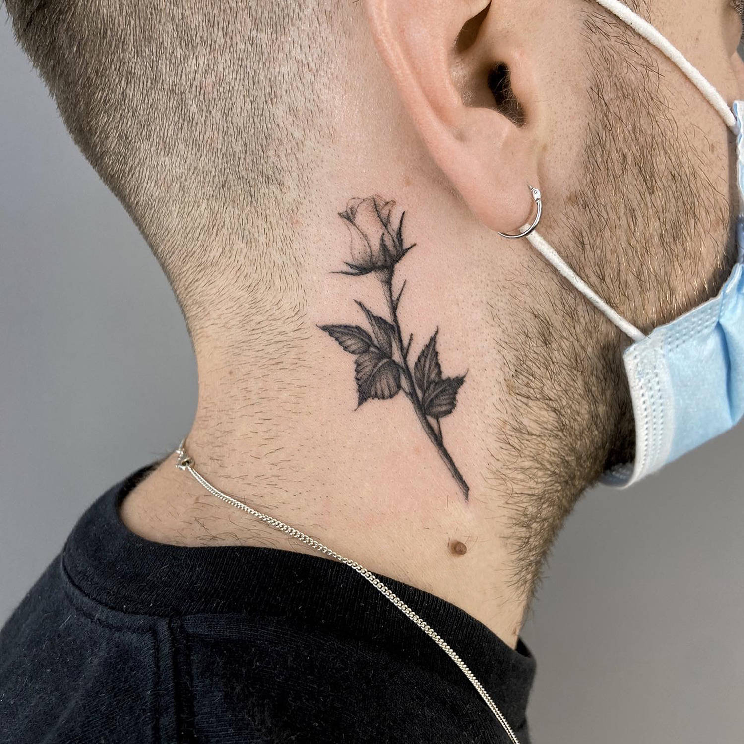 fine-line rose tattoo on neck, black ink