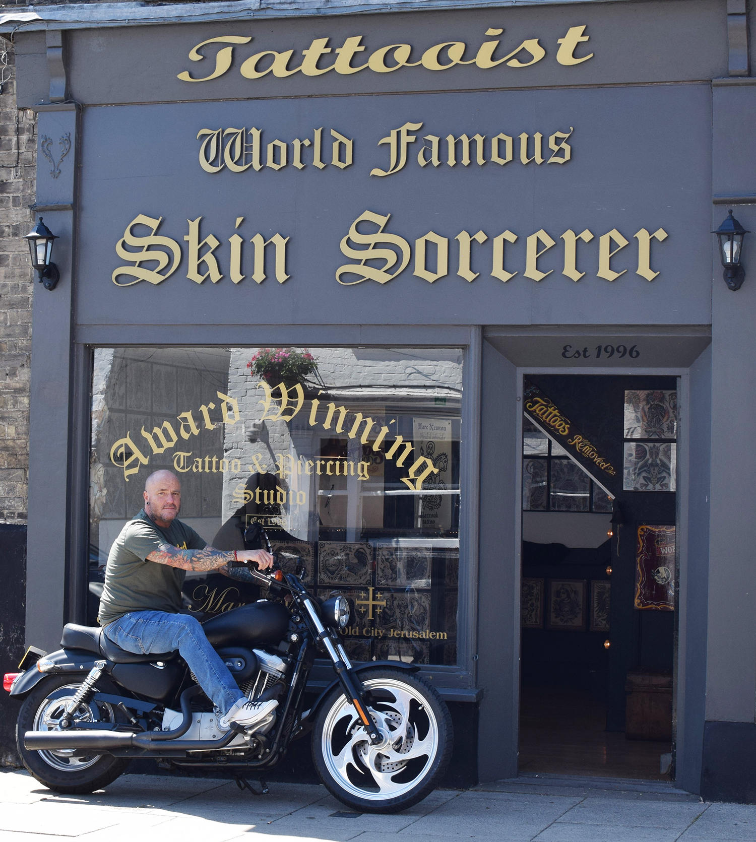 tattoo anthropologist Stephen c stratton on his motorcycle in front of the world famous skin sorcerer tattoo studio