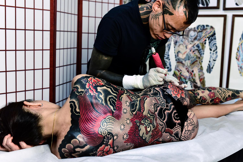"The artist working on a ""Karajishi Botan"" suit."