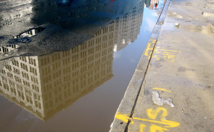 Buildings Reflected in Puddles